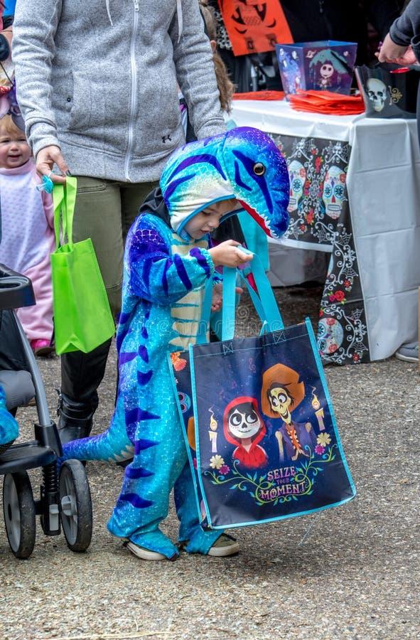 Ένα μικρό αγόρι σε ένα κοστούμι δεινοσαύρων κοιτάζει αδιάκριτα στην τσάντα καραμελών του για να δει όλες τις απολαύσεις μέσα στοκ εικόνες