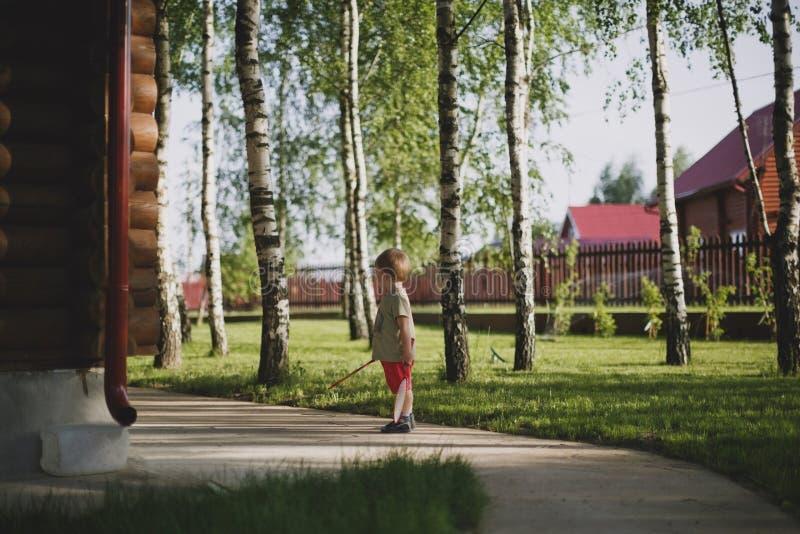 Ένα μικρό αγόρι στέκεται δίπλα σε ένα ξύλινο εξοχικό σπίτι που περιβάλλεται από τα δέντρα στοκ φωτογραφία με δικαίωμα ελεύθερης χρήσης