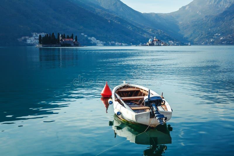 Ένα μικρό αλιευτικό σκάφος στον κόλπο Kotor στο Μαυροβούνιο ενάντια στο σκηνικό των βουνών, φωτεινό όμορφο τοπίο, καθαρίζει το νε στοκ εικόνες
