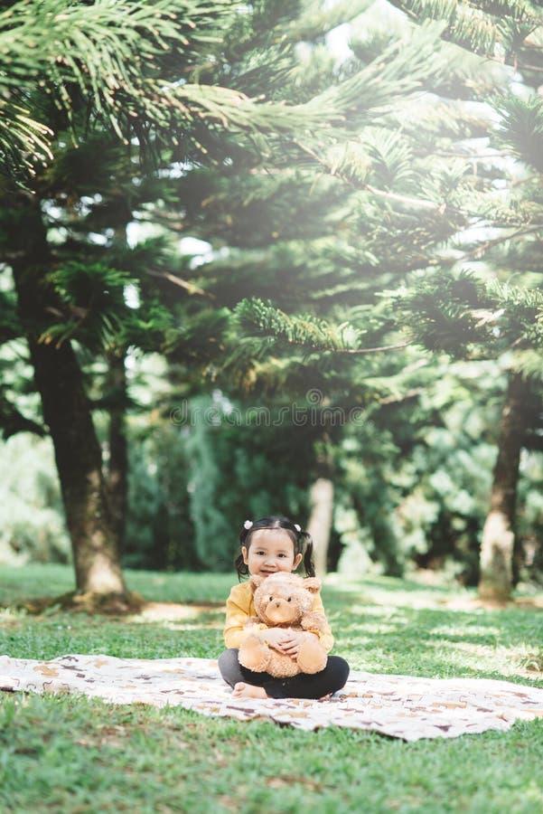 Ένα μικρό ασιατικό κορίτσι αγκαλιάζει το αρκουδάκι της σε ένα πάρκο στοκ φωτογραφία