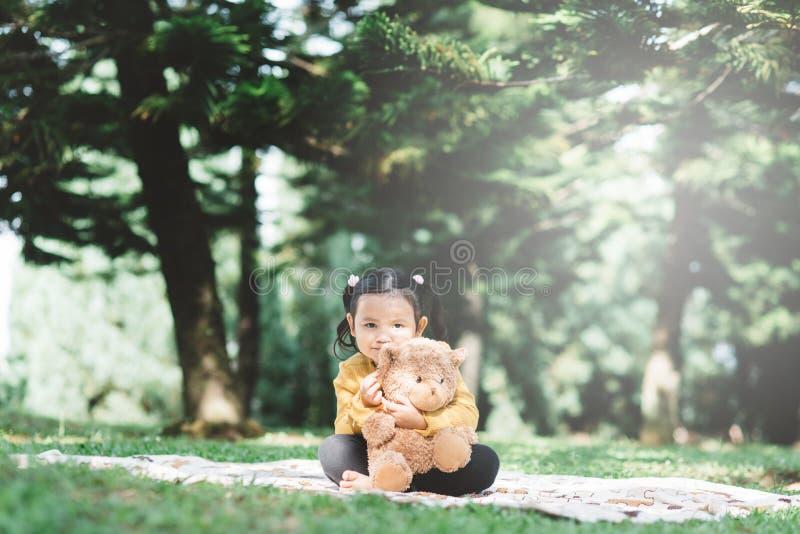 Ένα μικρό ασιατικό κορίτσι αγκαλιάζει το αρκουδάκι της σε ένα πάρκο στοκ εικόνες