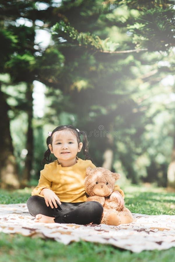 Ένα μικρό ασιατικό κορίτσι αγκαλιάζει το αρκουδάκι της σε ένα πάρκο στοκ φωτογραφία με δικαίωμα ελεύθερης χρήσης