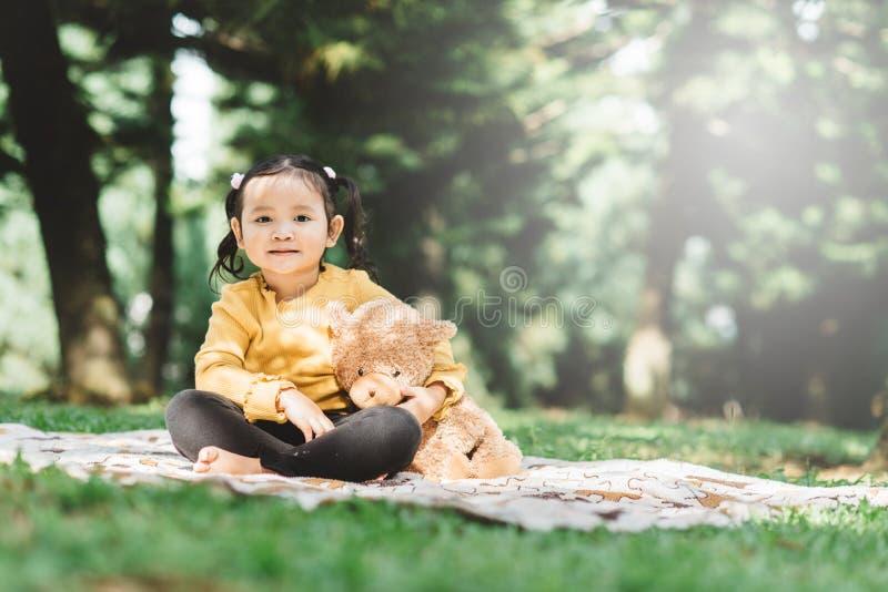 Ένα μικρό ασιατικό κορίτσι αγκαλιάζει το αρκουδάκι της σε ένα πάρκο στοκ φωτογραφίες