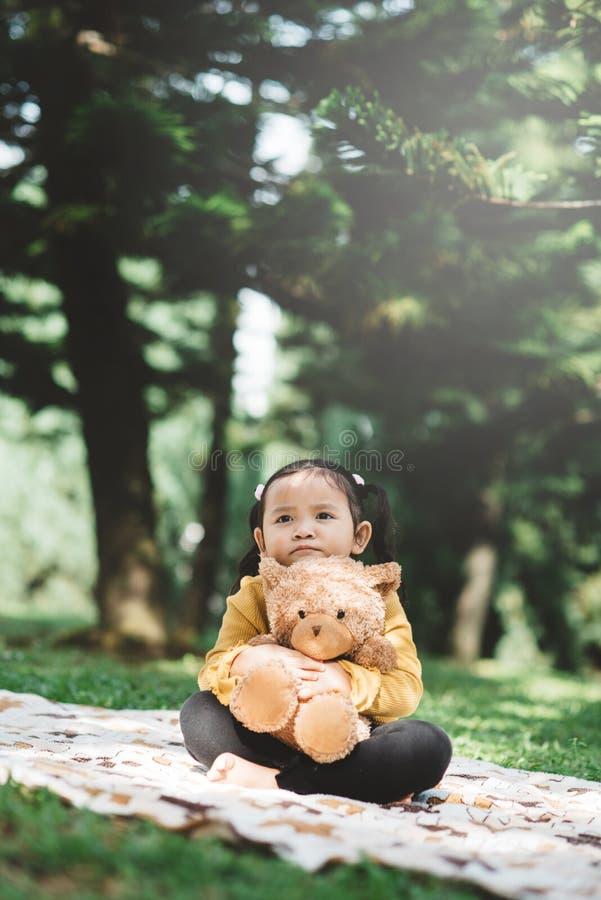 Ένα μικρό ασιατικό κορίτσι που κάθεται στο πάρκο ενώ αγκαλιάζει το αρκουδάκι της με θλιμμένο πρόσωπο στοκ εικόνα με δικαίωμα ελεύθερης χρήσης