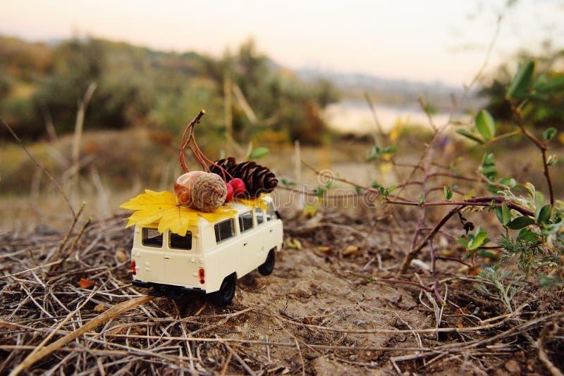 Ένα μικρό αυτοκίνητο παιχνιδιών minivan συνεχίζει τη στέγη ένα βελανίδι, μια πρόσκρουση και ένα κίτρινο φύλλο στο υπόβαθρο των δέ στοκ φωτογραφίες