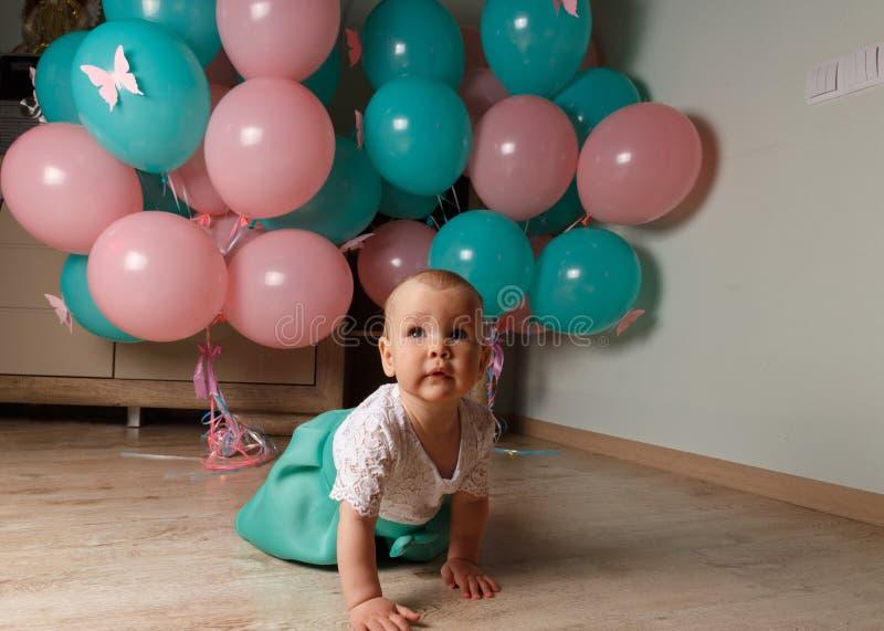 Ένα μικρό, γοητευτικό παιδί, ένα κορίτσι, γιορτάζει τα πρώτα γενέθλιά της, καθμένος δίπλα σε την με τα μπαλόνια Οργάνωση κόμματος στοκ εικόνες με δικαίωμα ελεύθερης χρήσης