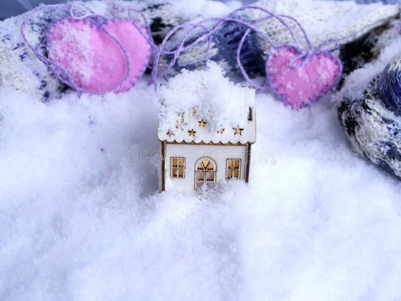 Ένα μικρό διακοσμητικό σπίτι παιχνιδιών με τον αναμμένο φωτισμό στο χιόνι στο υπόβαθρο ενός πλεκτού μαντίλι και των καρδιών αισθη στοκ εικόνα με δικαίωμα ελεύθερης χρήσης