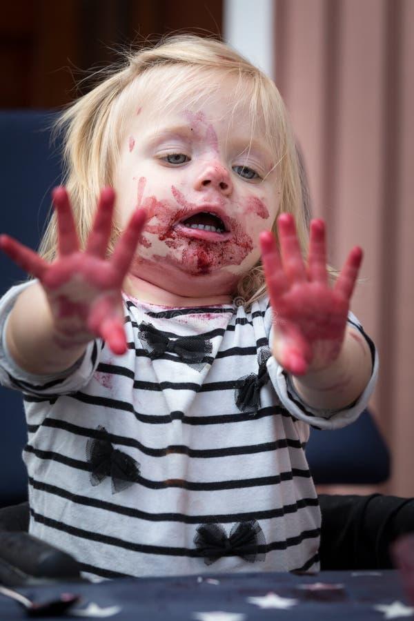 Ένα μικρό κορίτσι εξετάζει τα δάχτυλά της μετά από μια γιορτή βακκινίων στοκ εικόνες