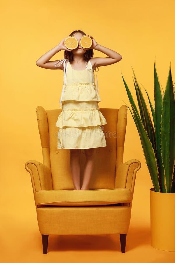 Ένα μικρό κορίτσι με κίτρινο φόρεμα, στέκεται σε μια κίτρινη καρέκλα σε ένα πορτοκαλί φόντο, κάνοντας πιτσουνάκια, κλείνοντας τον στοκ εικόνες με δικαίωμα ελεύθερης χρήσης