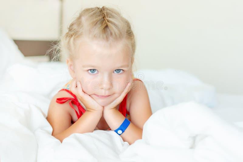 Ένα μικρό κορίτσι με τα ξανθά μαλλιά βρίσκεται σε ένα κρεβάτι με τα άσπρα linens Πορτρέτο ενός όμορφου παιδιού που χαμογελά και κ στοκ εικόνες