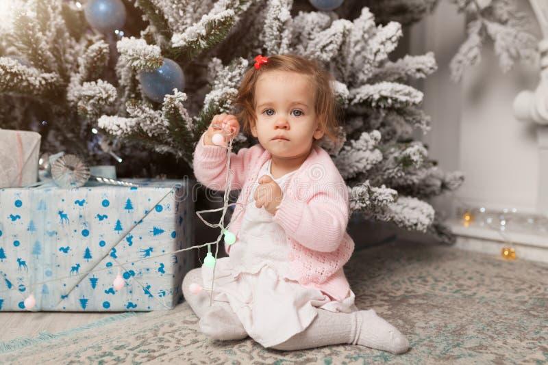 Ένα μικρό κορίτσι παίζει με μια γιρλάντα με ένα νέο δέντρο έτους κίνδυνος Απειθές παιδί Καλό νέο πνεύμα έτους στοκ εικόνα με δικαίωμα ελεύθερης χρήσης