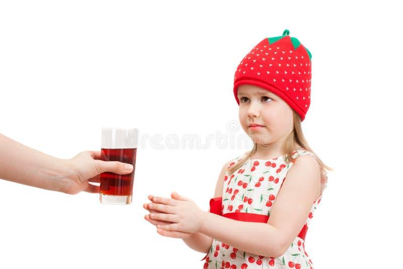 Ένα μικρό κορίτσι παίρνει ένα ποτήρι του χυμού μούρων στοκ φωτογραφία με δικαίωμα ελεύθερης χρήσης