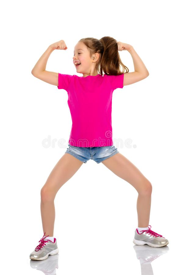 Ένα μικρό κορίτσι παρουσιάζει μυς της στοκ εικόνα