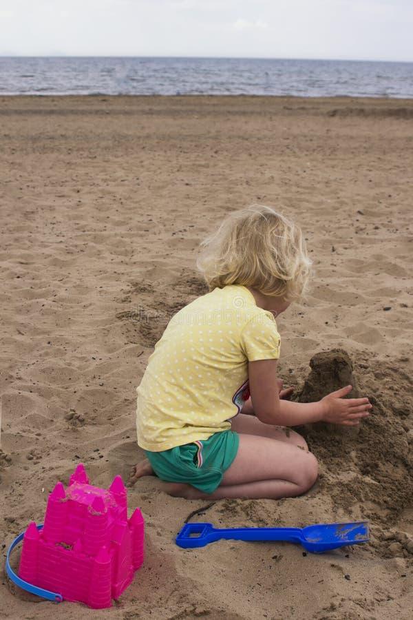 Ένα μικρό κορίτσι που διασκεδάζει χτίζοντας άμμους σε μια παραλία της Î στοκ εικόνα με δικαίωμα ελεύθερης χρήσης