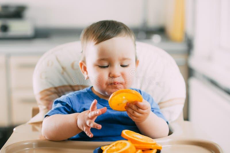 Ένα μικρό κορίτσι σε μια μπλε συνεδρίαση μπλουζών σε ένα κάθισμα παιδιών και την κατανάλωση ενός πορτοκαλιού στοκ φωτογραφίες