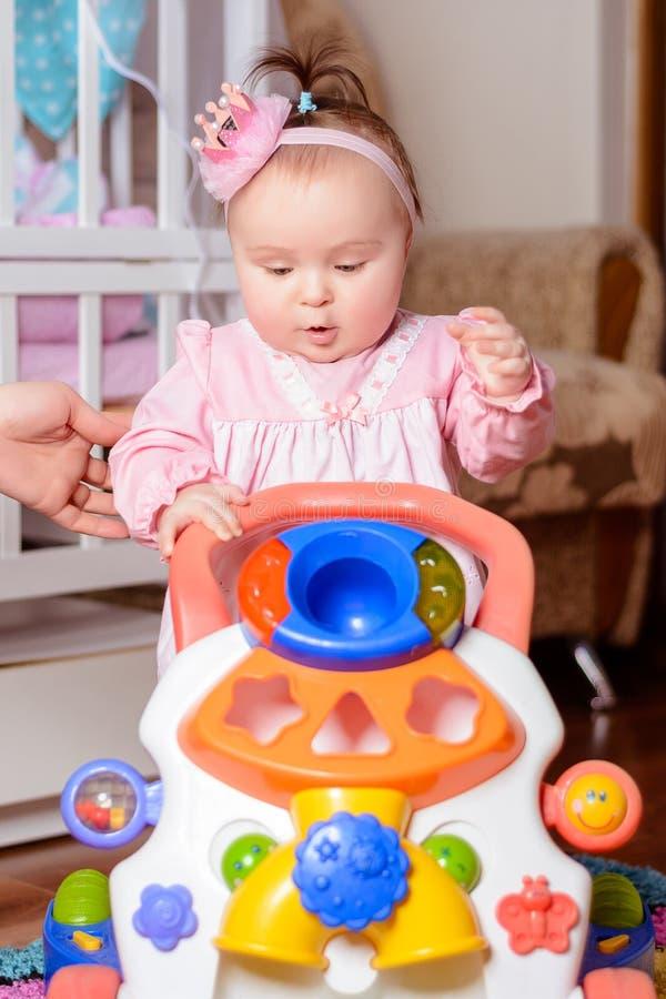 Ένα μικρό κορίτσι σε ένα ρόδινο φόρεμα παίζει ένα αυτοκίνητο παιχνιδιών κοντά στο παχνί στοκ φωτογραφίες
