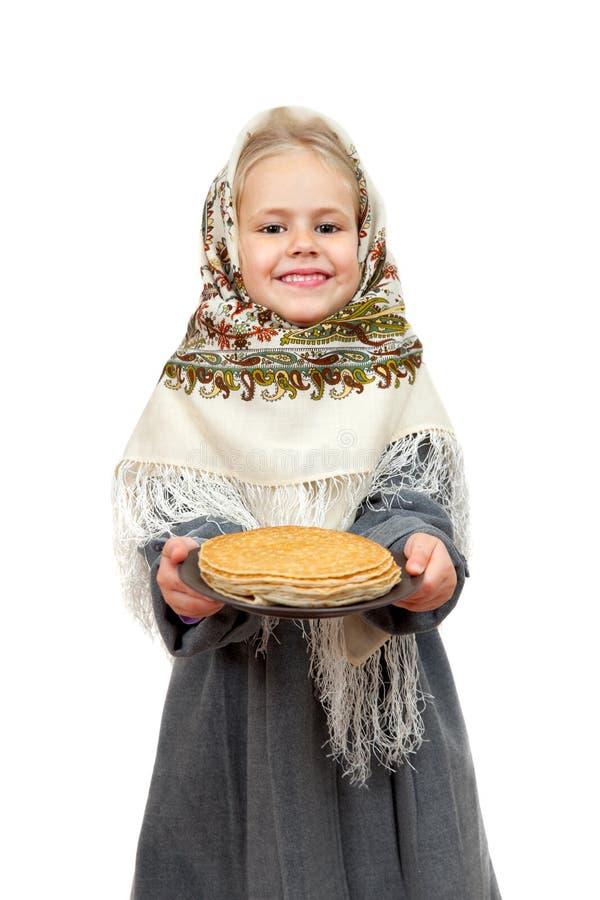 Ένα μικρό κορίτσι στο παραδοσιακό ρωσικό μαντίλι για το κεφάλι με ένα πιάτο των τηγανιτών στοκ φωτογραφία