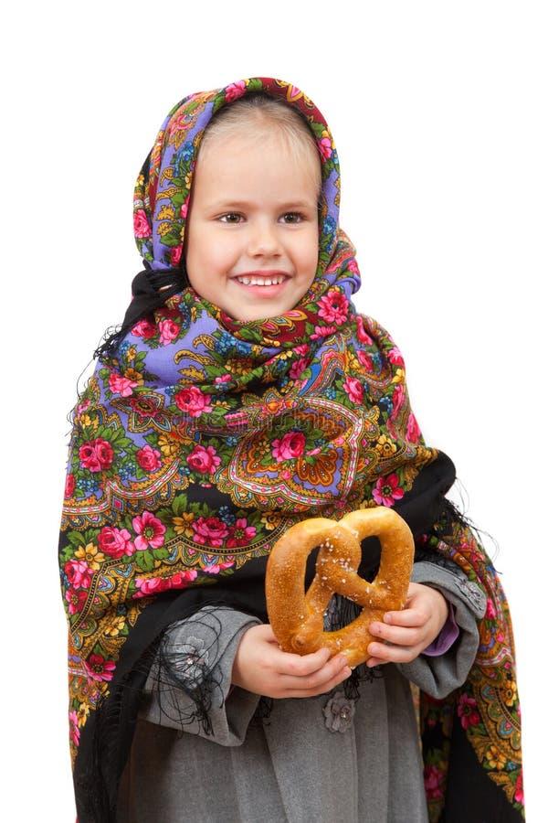 Ένα μικρό κορίτσι στο παραδοσιακό ρωσικό μαντίλι για το κεφάλι με pretzel στοκ φωτογραφία με δικαίωμα ελεύθερης χρήσης
