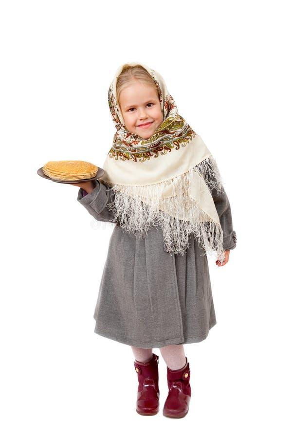 Ένα μικρό κορίτσι στο παραδοσιακό ρωσικό μαντίλι για το κεφάλι που κρατά ένα πιάτο των τηγανιτών στοκ εικόνα με δικαίωμα ελεύθερης χρήσης