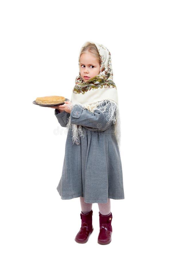 Ένα μικρό κορίτσι στο παραδοσιακό σλαβικό μαντίλι για το κεφάλι κρατά ένα πιάτο των τηγανιτών στοκ εικόνες