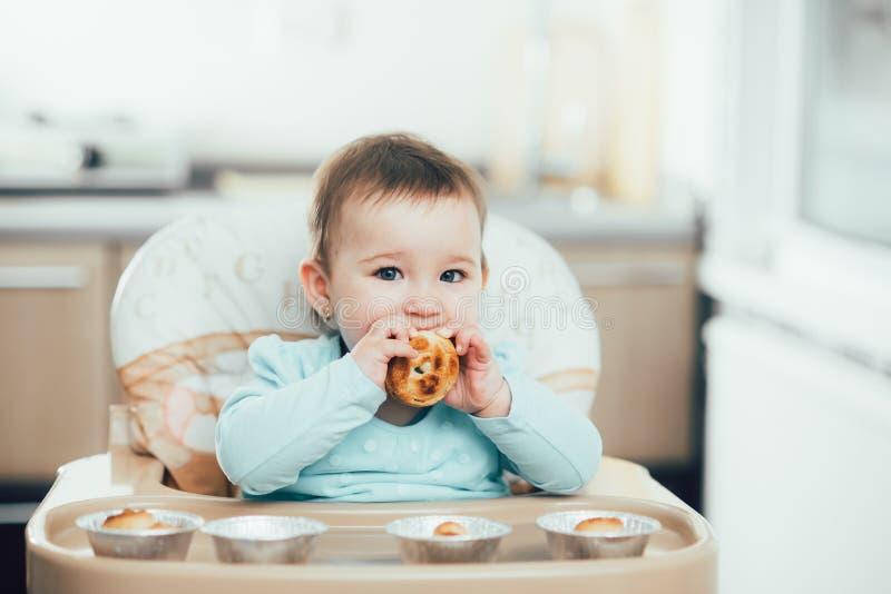 Ένα μικρό κορίτσι στο highchair τρώει Krapina, όπως muffins και croissants στοκ εικόνες