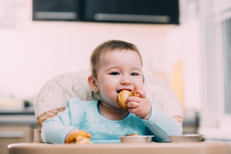 Ένα μικρό κορίτσι στο highchair τρώει Krapina, όπως muffins και croissants την τάση στοκ εικόνες