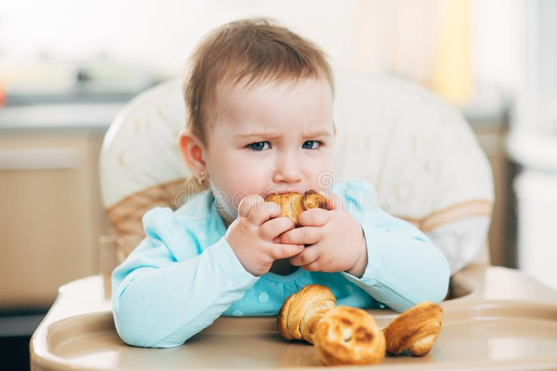 Ένα μικρό κορίτσι στο highchair τρώει Krapina, όπως muffins και croissants στοκ φωτογραφίες