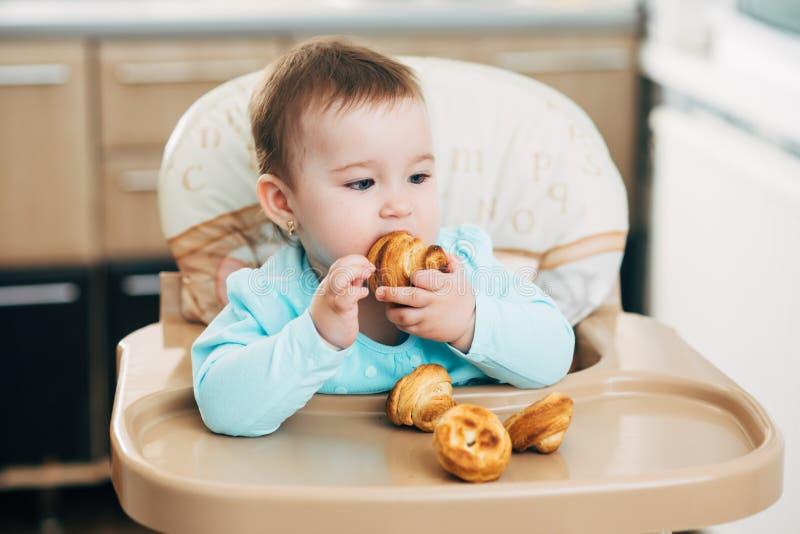 Ένα μικρό κορίτσι στο highchair τρώει Krapina, όπως muffins και croissants στοκ φωτογραφία