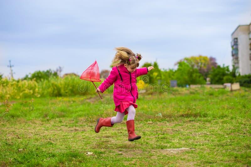 Ένα μικρό κορίτσι τρέχει με την πεταλούδα καθαρή που έχει τη διασκέδαση στοκ φωτογραφία με δικαίωμα ελεύθερης χρήσης