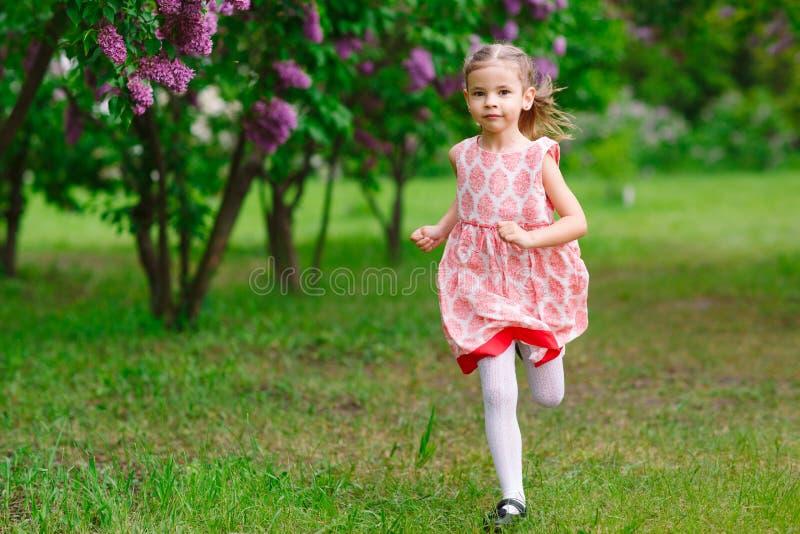 Ένα μικρό κορίτσι τρέχει στο πάρκο υπαίθρια στοκ εικόνες με δικαίωμα ελεύθερης χρήσης