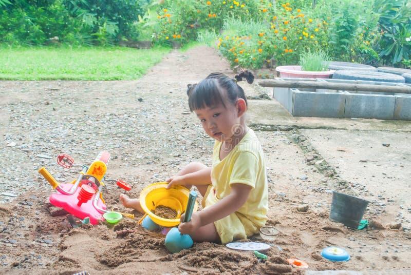 Ένα μικρό κορίτσι 4-5 χρονών παίζει στην άμμο στον κήπο στοκ φωτογραφία με δικαίωμα ελεύθερης χρήσης