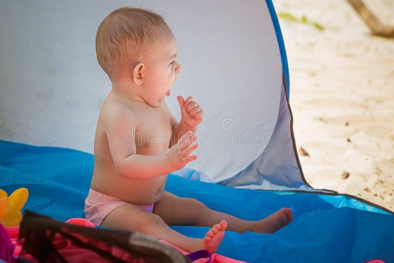 Ένα μικρό μωρό κάθεται σε μια σκηνή που προφυλάσσεται από τον ήλιο στην παραλία και τα χασμουρητά Θελήστε να κοιμηθείτε στοκ φωτογραφία με δικαίωμα ελεύθερης χρήσης