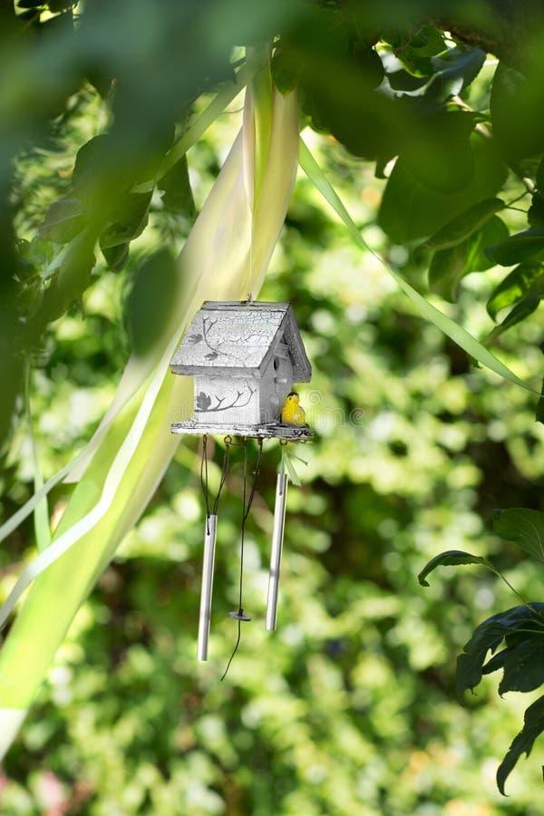 Ένα μικρό ξύλινο γκρίζο να τοποθετηθεί κιβώτιο με ένα κίτρινο πουλί στο φυσικό υπόβαθρο Το όμορφο birdhouse στο πράσινο πάρκο Το  στοκ φωτογραφίες με δικαίωμα ελεύθερης χρήσης