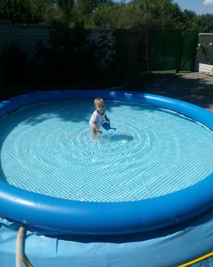 Ένα μικρό παιδί κάθεται στη λίμνη και τα χαμόγελα, παιχνίδια, ο ήλιος λάμπουν καλοκαίρι στοκ εικόνα με δικαίωμα ελεύθερης χρήσης