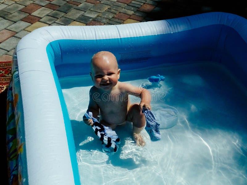 Ένα μικρό παιδί κάθεται στη λίμνη και τα χαμόγελα, παιχνίδια, ο ήλιος λάμπουν καλοκαίρι στοκ εικόνες