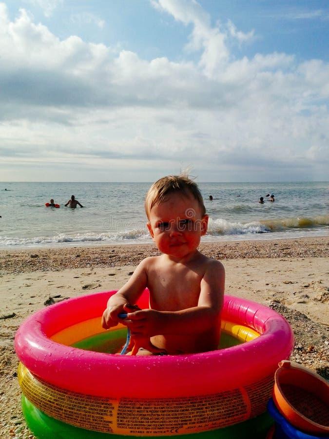 Ένα μικρό παιδί κάθεται στη λίμνη και τα χαμόγελα, παιχνίδια, ο ήλιος λάμπουν καλοκαίρι στοκ φωτογραφίες με δικαίωμα ελεύθερης χρήσης