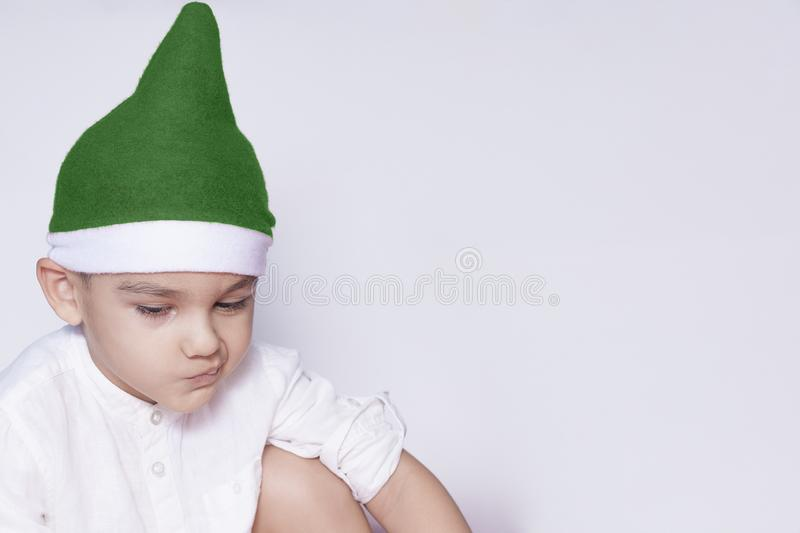 Ένα μικρό παιδί που κάνει ένα αστείο ενοχλημένο πρόσωπο Ενοχλημένο αγόρι Χριστουγέννων στο καπέλο Santa Ένα πραγματικά σοβαρό και στοκ εικόνα με δικαίωμα ελεύθερης χρήσης