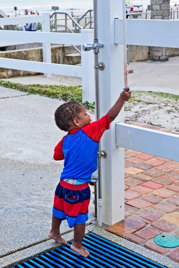 Ένα μικρό παιδί προσπαθεί να πλημμυρίσει μακριά σε ένα υπαίθριο ντους στην παραλία στοκ φωτογραφία με δικαίωμα ελεύθερης χρήσης
