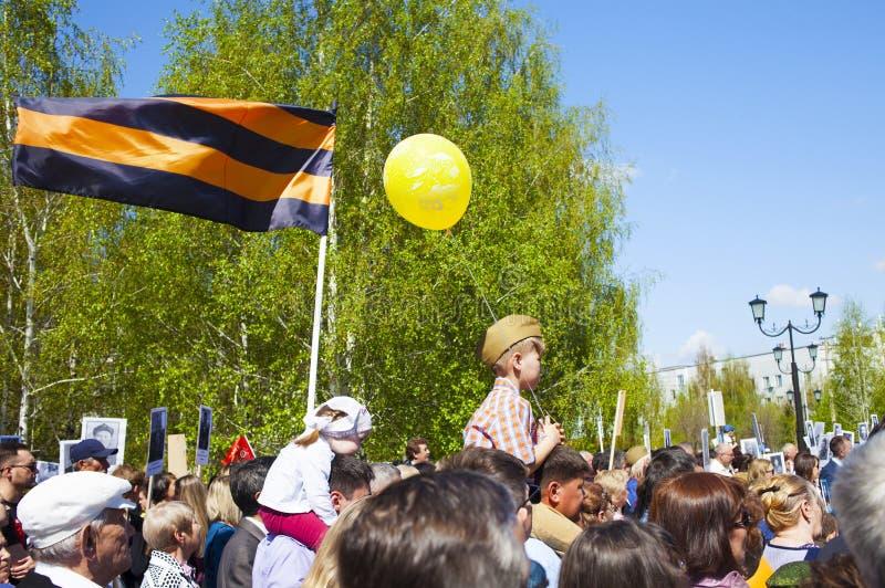 Ένα μικρό παιδί στους ώμους του πατέρα του 9 Μαΐου, ημέρα νίκης Κορδέλλα του ST George στοκ φωτογραφία με δικαίωμα ελεύθερης χρήσης