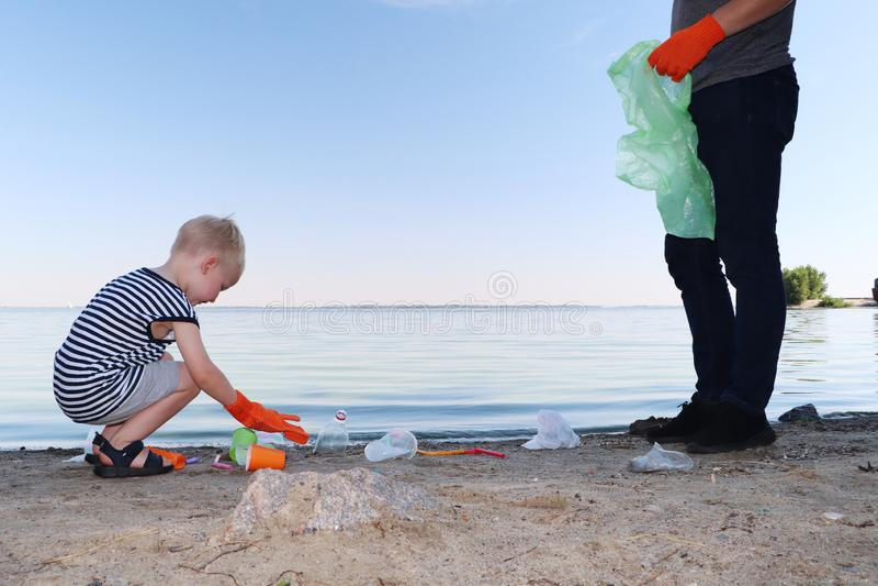 Ένα μικρό παιδί συλλέγει τα απορρίμματα στην παραλία Ο μπαμπάς του δείχνει το δάχτυλό του πού να ριχτούν τα απορρίματα Οι γονείς  στοκ εικόνες με δικαίωμα ελεύθερης χρήσης