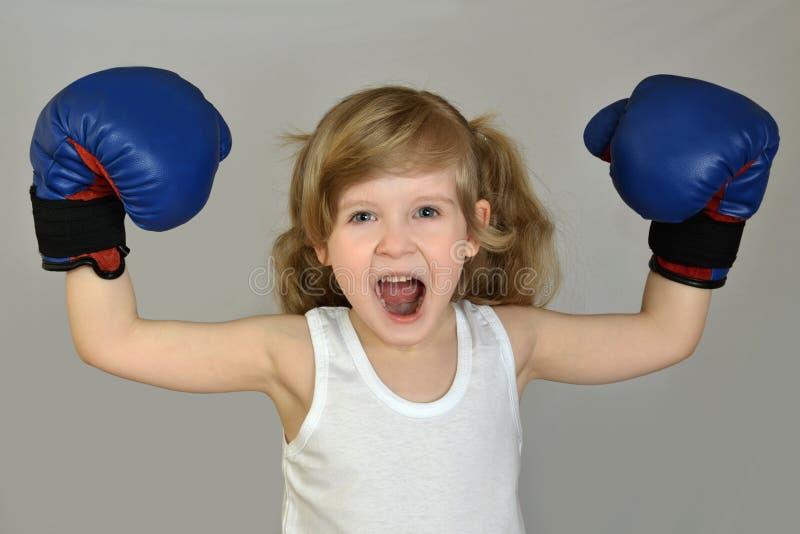 Ένα μικρό παιδί κοριτσιών, παιδί στα εγκιβωτίζοντας γάντια στοκ εικόνες