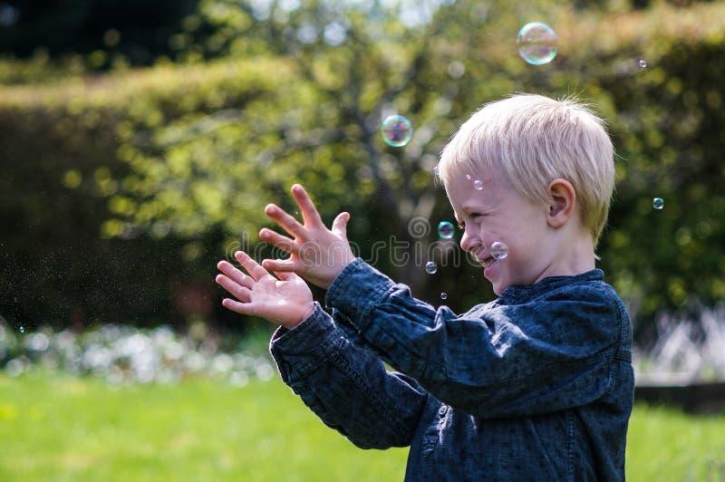 Ένα μικρό παιδί φυσά τις φυσαλίδες σαπουνιών στον κήπο μια θερινή ημέρα στοκ εικόνα με δικαίωμα ελεύθερης χρήσης