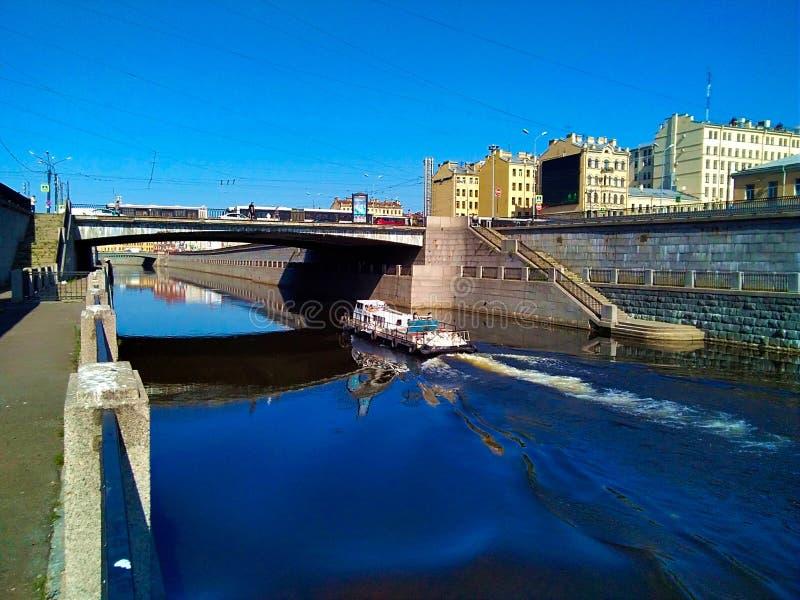 """Ένα μικρό πλοίο επιπλέει στο νερό κάτω από τις γέφυρες Ï""""Î¿Ï… καναλιού στη στοκ εικόνες"""