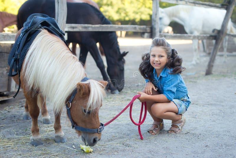 Ένα μικρό χαμογελώντας κορίτσι με τη σγουρή τρίχα έντυσε στα τζιν ταΐζοντας ένα πόνι στο σταύλο στοκ φωτογραφία με δικαίωμα ελεύθερης χρήσης