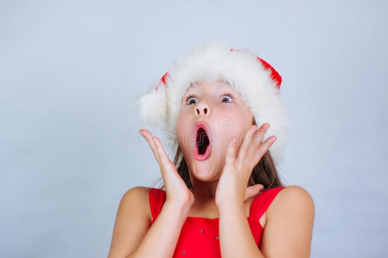 ένα μικρό χαριτωμένο κορίτσι στέκεται σε ένα χριστουγεννιάτικο καπέλο και εκπλήσσεται από τις γιορτές στοκ εικόνα με δικαίωμα ελεύθερης χρήσης