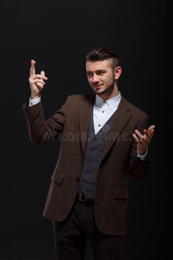 Ένα μοντέρνο άτομο παρουσιάζει κάτι σε ετοιμότητα του σε ένα μαύρο κλίμα στοκ φωτογραφίες
