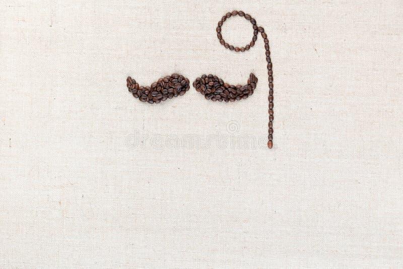 Ένα μονόκλ και ένα mustache έκαναν με τα φασόλια καφέ που βλασταήθηκαν άνωθεν, ευθυγραμμισμένος στην κορυφή στοκ φωτογραφίες