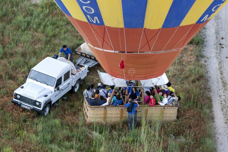 Ένα μπαλόνι ζεστού αέρα φόρτωσε με τα ασιατικά εδάφη τουριστών σε μια μάντρα κοντά σε Goreme στην Τουρκία στοκ εικόνες