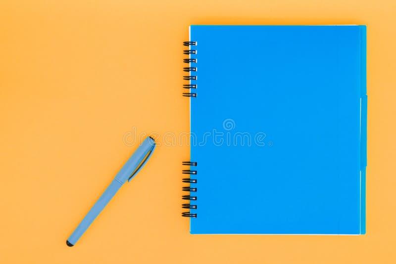 Ένα μπλε σημειωματάριο με μια λαβή στο πορτοκαλί υπόβαθρο Επίπεδος βάλτε το πρότυπο τοποθετήστε το κείμενο στοκ εικόνες