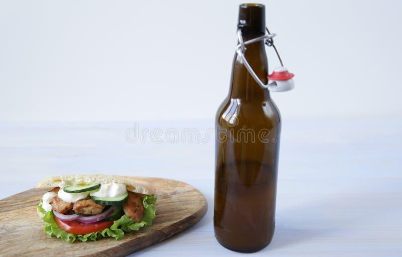Ένα μπουκάλι της μπύρας και Pita - ένα σάντουιτς, sabiche γεμισμένος με το κοτόπουλο, τη σάλτσα, τις ντομάτες, τα αγγούρια και τη στοκ εικόνα με δικαίωμα ελεύθερης χρήσης
